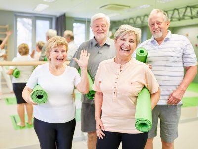 Glückliche Senioren mit Yogamatten im Sportstudio freuen sich auf die Rückengymnastik